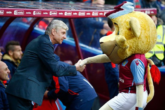 فينجر مدرب أرسنال يصافح تميمة استون فيلا قبل لقاء الفريقين