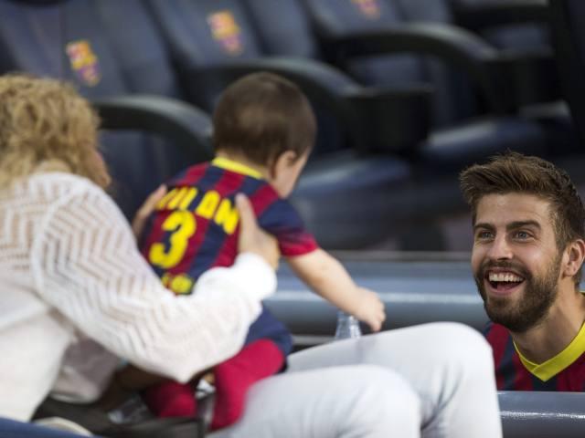 GRA396. BARCELONA, 14/09/2013.- El defensa del FC Barcelona Piqué (d) saluda a su hijo Milan, al inicio del partido de la cuarta jornada de Liga ante el Sevilla disputado esta noche en el Camp Nou, en Barcelona. EFE/Alejandro García